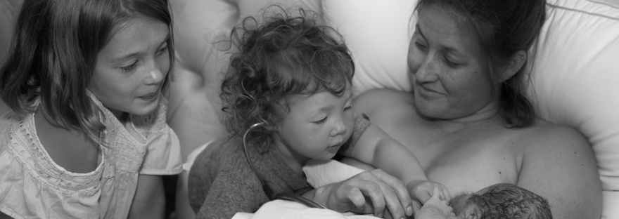 Siblings greeting the newborn baby